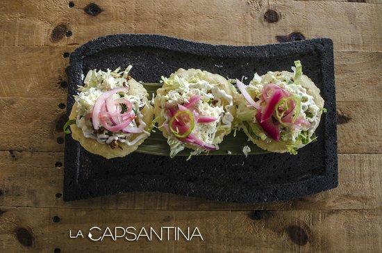 "La Capsantina: ""Papadzules"" Tortillas de maíz, rellenas de cochinita pibil, bañadas en salsa de pipian."