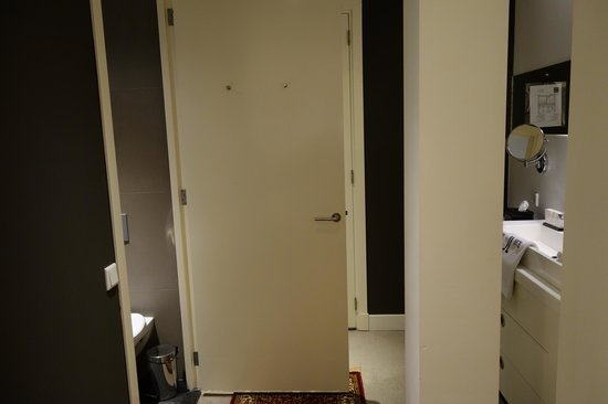Hotel JL No76 : Room door with sink to the right and bathroom door on the left.