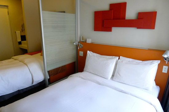 Citadines Shinjuku Tokyo: Double Bed and a Sofa Pull Away Bed that has a glass door separating both beds