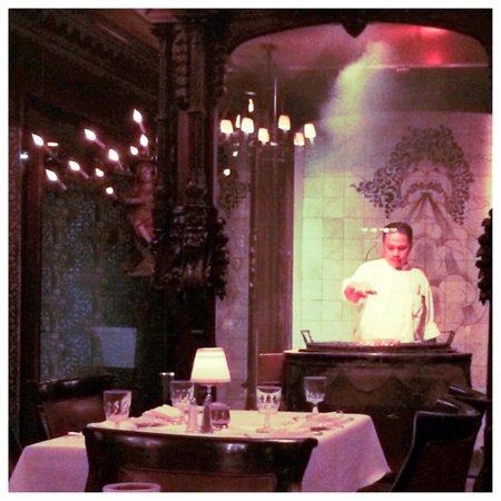 Hy's Steak House - Waikiki: A chef cooking in a glass and mahogany area in the dining room