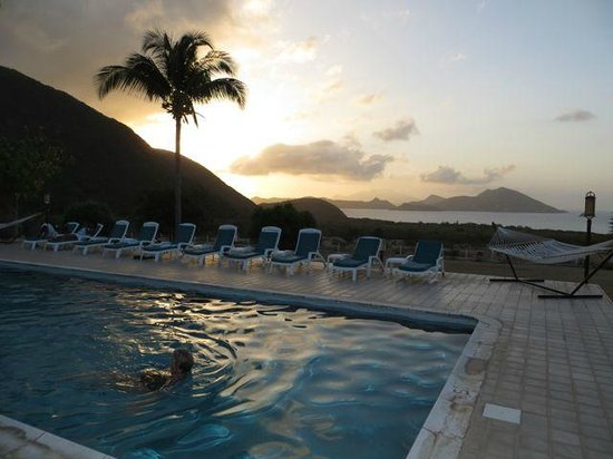 The Mount Nevis Hotel: My wife swimming in the pool at sunset.