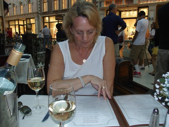 Trattoria Reggiano: Studying the menu at our favourite table!!