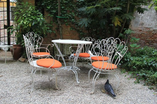 Hotel Flora: Chairs and Tables in the backyard