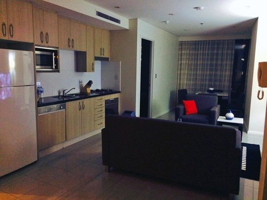 Meriton Serviced Apartments Pitt Street : Kitchen and lounge area (by night) of a 1 bedroom apartment.