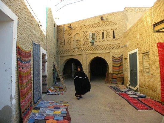 Le Vieux Quartier de Ouled el Hadef (Medina) : Via della Medina con negozi di artigianato e una donna in costume tipico