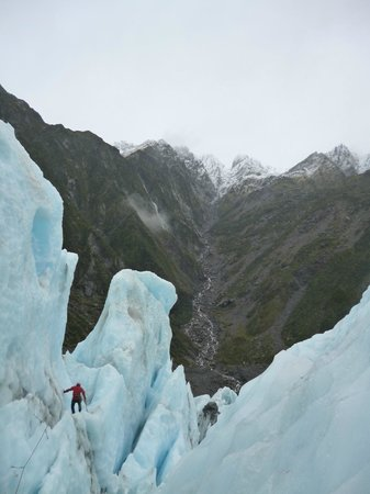 Franz Josef Glacier Guides: Guide is dwarfed by the ice as he prepares a path for us