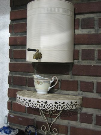 Tuck U Inn at Glick Mansion: Love this water cooler attached to the brick wall on the front screened porch.