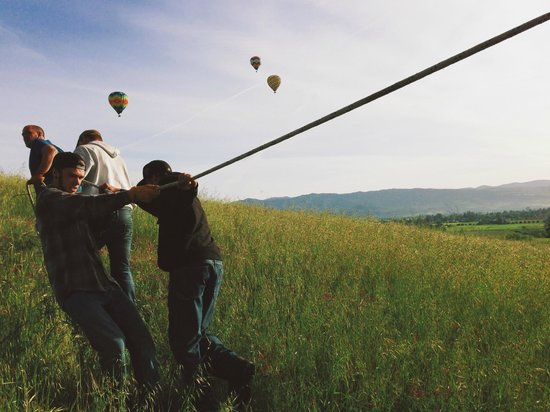 Balloons Above the Valley: crew pulling our balloon up the hill to land safely