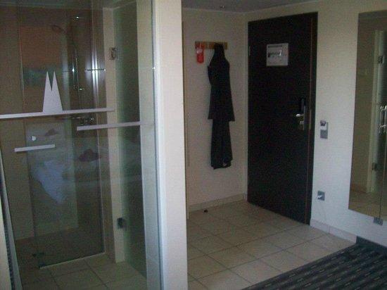 Hotel Lyskirchen: Blick auf Zimmertür/Garderobe, links neben dem Mantel befindet sich ein Kleiderschrank mit Safe