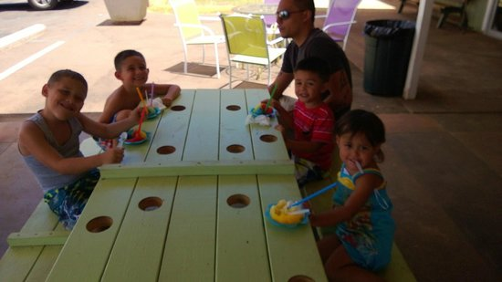 Ululani's Hawaiian Shave Ice: Kids enjoying their shaved ice with tables made to hold their cups!
