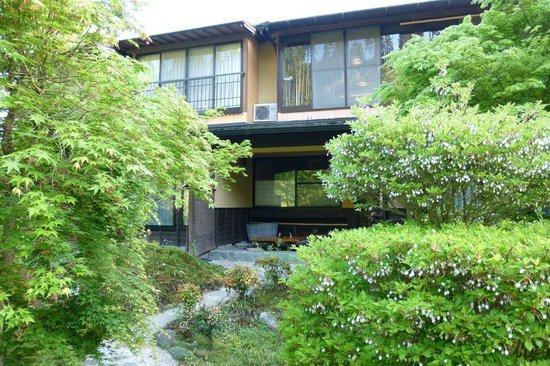 Kosugian: 外観。1階に足湯(写真正面)があります。木々の間を抜けてお風呂へ。