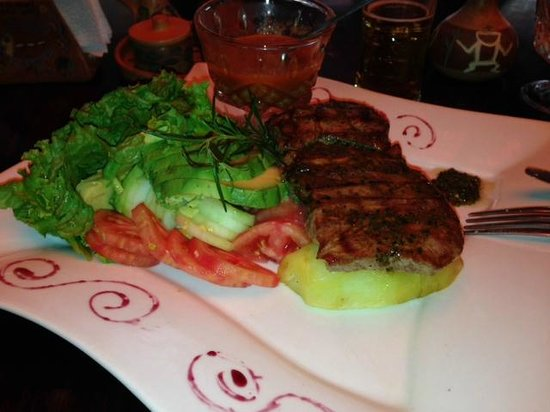 Inka Wasi Restaurant and Pizzeria: grilled alpaca. there are 2 slabs of meat one under the other. with avocado, tomato, cucumber