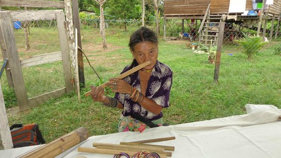 Mulu Caves : A villager playing the flute through her nose