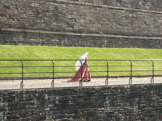 Carlisle Castle: Actor in period dress walking along the bridge.