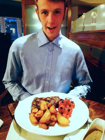 Big Blue Hotel: My fiancé enjoying steak and chips! The steak was amazing! Melted in your mouth, beautiful!