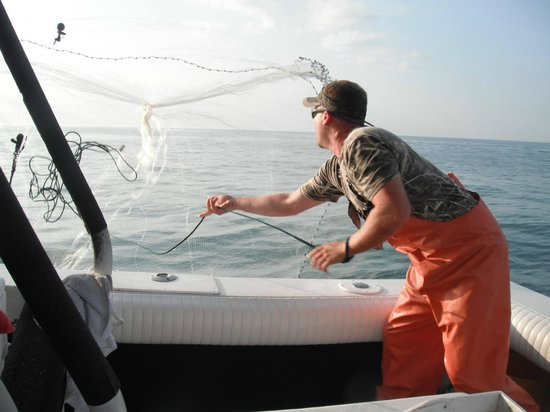 Arts Adventures - Private Charters: Daniel casting the net for bait.