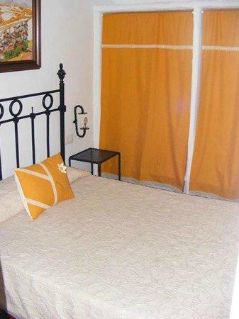 Apartamentos San Anton : Dormitorio con cortinas en el armario