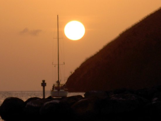 The Landings Resort & Spa St. Lucia: A sailboat in the sunset by Pigeon Island, from the resort's beach.
