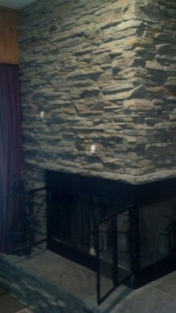 Golden Eagle Resort : A corner fireplace with logs and kindling in our room.