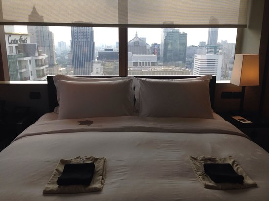The Okura Prestige Bangkok: Corner suit bed with Bangkok out the window