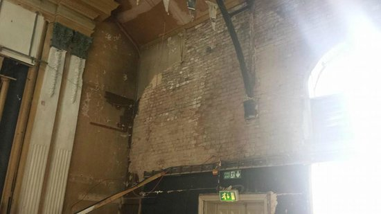 The Grand Pavilion, Matlock Bath: to the right of the stage where the plaster has fallen off the wall