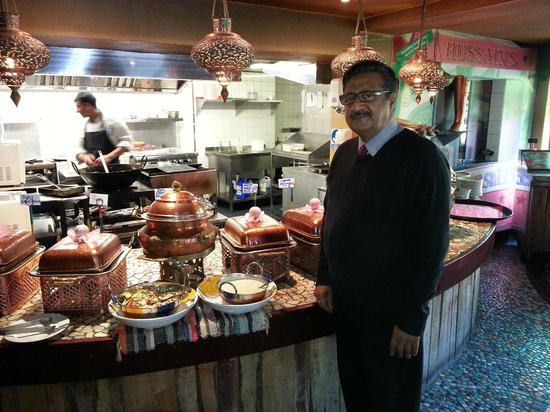 Hussain's: Mr.Khan in front of the buffet, cook in kitchen background