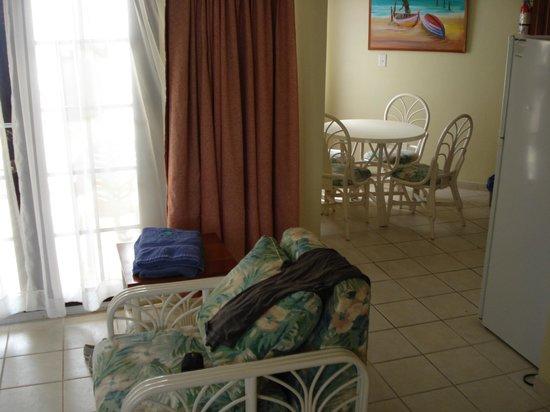 SunBreeze Suites: dos a la porte d'entrée sur le debut du salon et de la cuisine