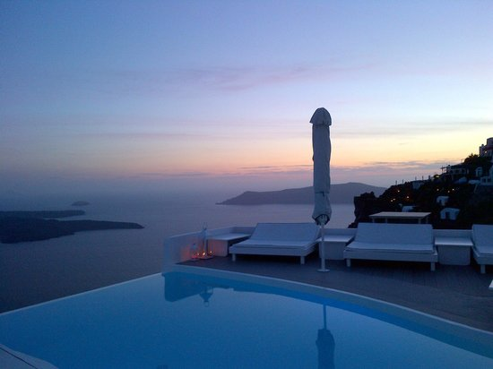 Chromata Hotel : The pool area at sunset, looking towards Oia
