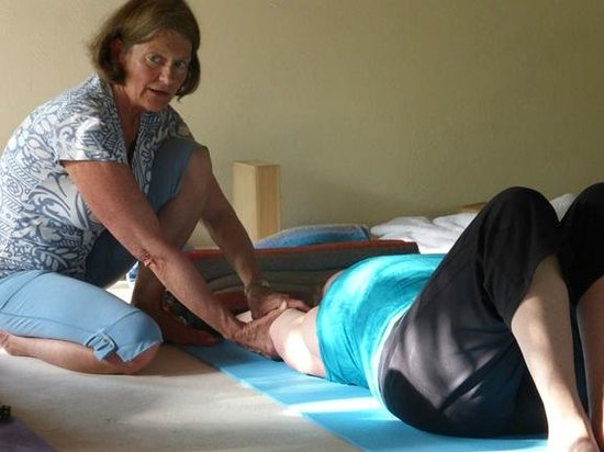 Petit Lafitte: Nancy adjusting student in yoga.