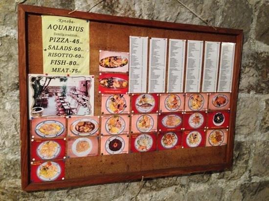 Aquarius: Detailed menu board on the wall facing the restaurant.