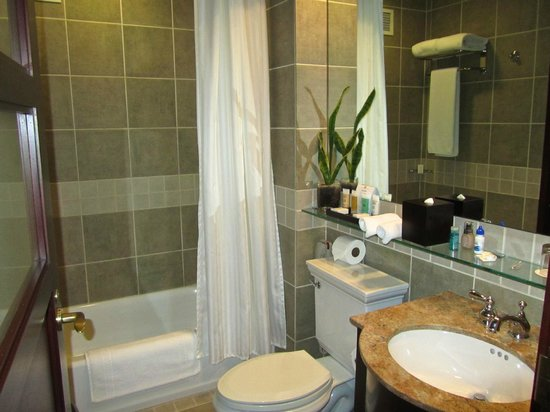 Library Hotel by Library Hotel Collection: Bathroom with ample shelf space for toiletries