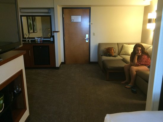 Hyatt Place OKC Airport: Sectional sofa with pull out. Corner bar area with fridge and desk opposite wall. Room 518