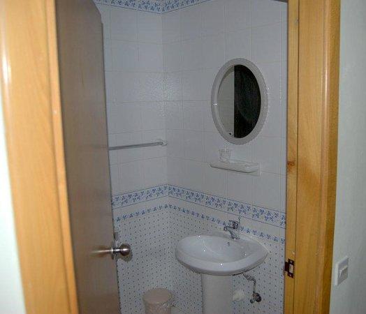 115 The Strand Hotel and Suites : Bagno scomodo pezzi bassi vasca con tenda plastica appiccicosa