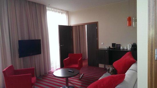 Mercure Warsaw Grand: Lounge area in room, with door to bedroom