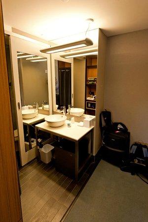Aloft New York Brooklyn: Waschbereich, links davon Dusche, im Spiegel ist der Safe und Kaffeemaschine zu sehen