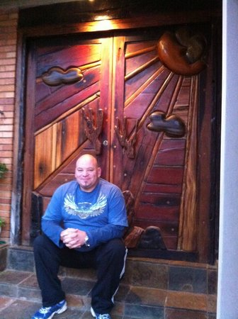 Sunrock Guesthouse: Chris (charming proprietor) sits outside gorgeous hand-carved door to the grounds.