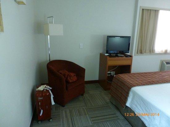Comfort Suites Brasília: Poltrona confortável e aparador para TV.