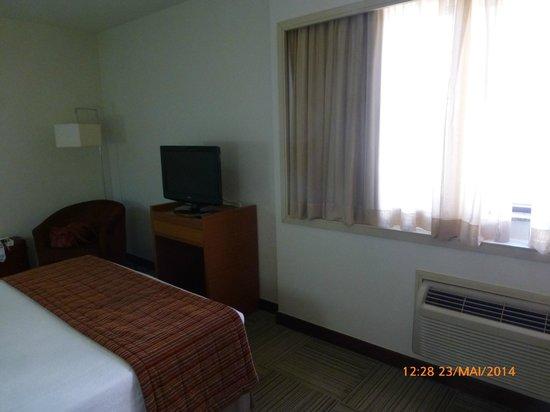 Comfort Suites Brasília: Aparador da TV e poltrona aptº 214