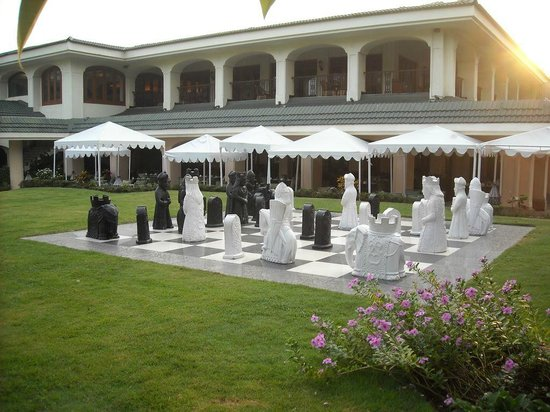 Taj Exotica Goa: The outdoor chess board with the hotel in the backgraond