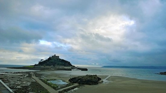 Godolphin Arms: View from the balcony rooms to St Michael's Mount on a cloudy day at low tide.