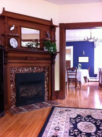 Brewster House Bed & Breakfast: Beautiful fireplace in front parlor with dining area in view