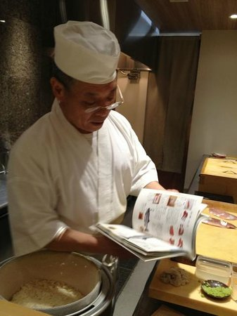 Sushi Bar Yasuda: Yasuda looking through his book of fish to explain to us
