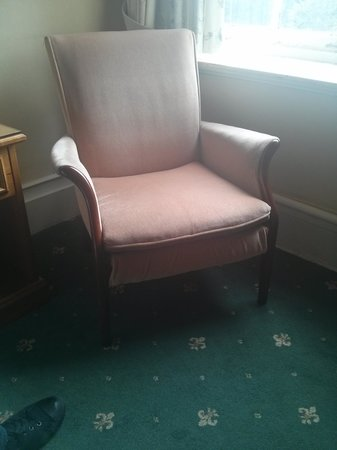 The Ripon Spa Hotel: faded, dated ripped chair that looks like it came from a nursing home