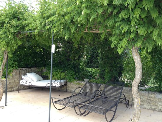 Le Mas au Portail Bleu: Sitting area in front of pool under a shady trellis