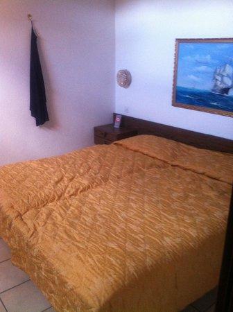 Hotel Dell'Angelo: photo prise depuis porte entrée chambre, la table de nuit à droite touche également le mur