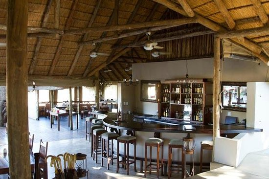 Simbavati River Lodge: bar in main lodge.  dining area in distance