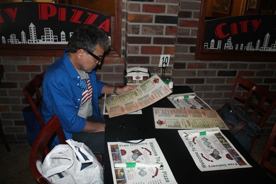 City Pizza Italian Cuisine: Edu lendo o menu do City Pizza.