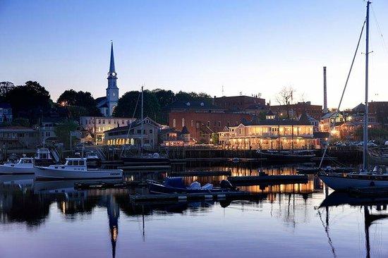 View of Grand Harbor Inn from across Camden Harbor at dusk.