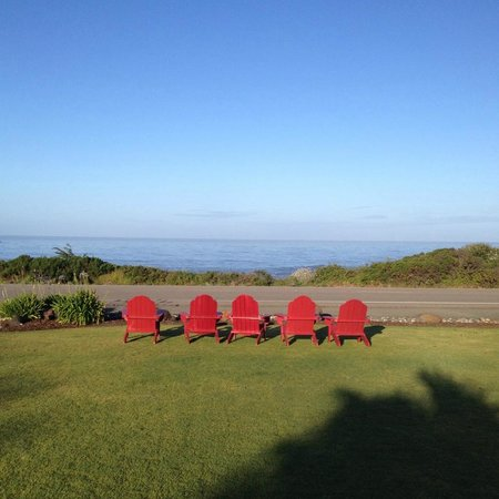 Castle Inn's red Adirondack chairs facing Moonstone Boardwalk and the vast Pacific.