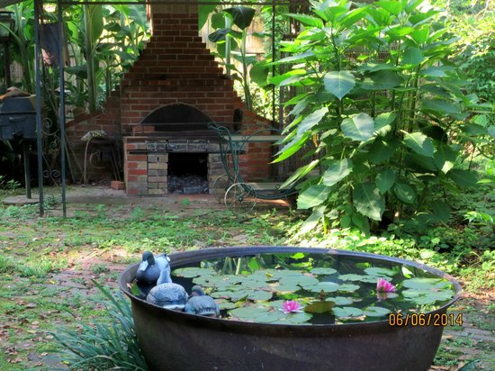 Bois des Chenes: an old South view of the backyard - fireplace & water feature